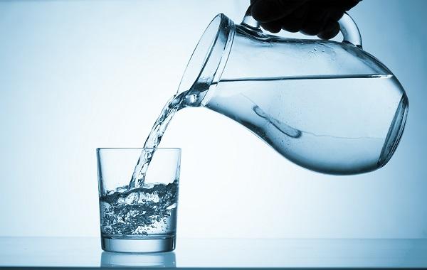 woda nalewana z dzbanka do szklanki